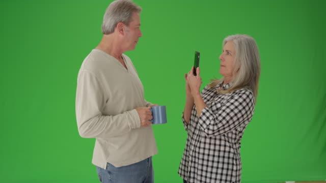 stockvideo's en b-roll-footage met portrait of a mature white couple looking at a cellular device - natuurlijk haar