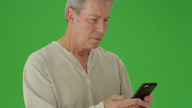 Portrait of a mature white man texting in front of green screen