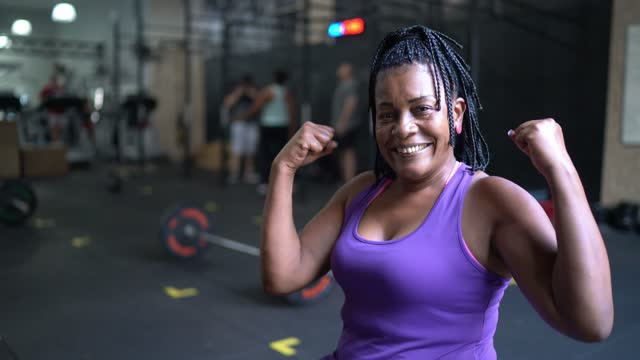 portrait of a mature woman flexing muscles in the gym - exercise machine stock videos & royalty-free footage
