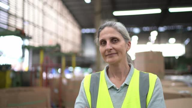 vídeos de stock e filmes b-roll de portrait of a mature woman in a distribution warehouse - trabalhador manual