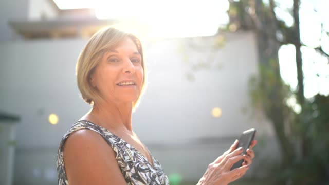 portrait of a mature woman in front of a house - in front of stock videos & royalty-free footage