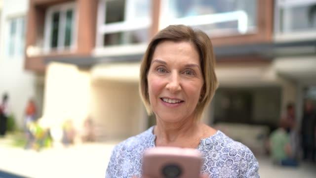 stockvideo's en b-roll-footage met portret van een volwassen vrouw voor een huis - voor of achtertuin