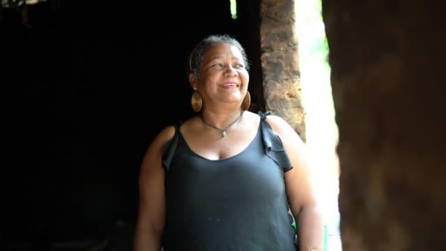 ワトルと塗りつけるの家の前で成熟した女性の肖像 - アフリカ系カリブ人点の映像素材/bロール