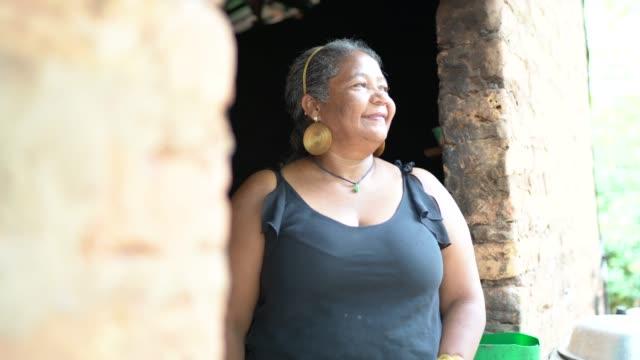 vídeos de stock, filmes e b-roll de retrato de uma mulher madura na frente de uma casa do wattle e do daub - esperança conceito