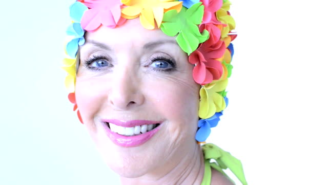 portrait of a mature woman with floral swimming cap - swimming cap stock videos and b-roll footage