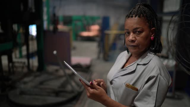 portrait of a mature woman working using a digital tablet in a factory - real people stock videos & royalty-free footage