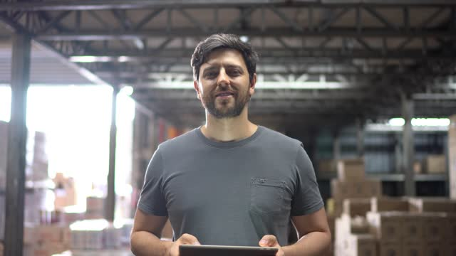 portrait of a mid adult man in a warehouse using a digital tablet - business stock videos & royalty-free footage