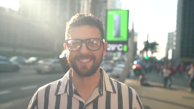 vídeos de stock, filmes e b-roll de retrato de um homem adulto meados de em uma avenida - brasileiro pardo