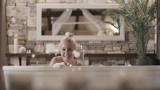 slo mo portrait of a mid adult woman having fun while taking a bubble bath - soap sud video stock e b–roll