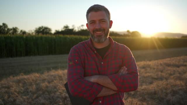 vídeos y material grabado en eventos de stock de retrato de un agricultor moderno de mediana edad de pie con los brazos cruzados en el campo de trigo al atardecer - bien parecido