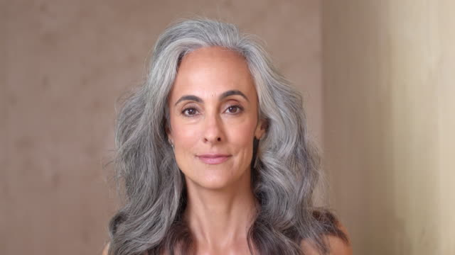 vidéos et rushes de portrait of a middle-aged woman looking into camera smiling, against a wooden background - only women