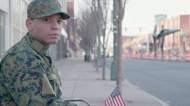 portrait of a military man holding a us flag - war veteran stock videos & royalty-free footage