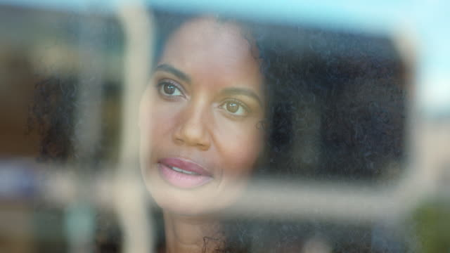 Portrait of a mixed race, middle-aged woman with natural hair smiling while looking outside through window.