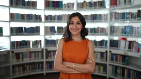 vidéos et rushes de portrait d'une femme de race mixte souriant dans la bibliothèque de l'école - cadrage à la taille