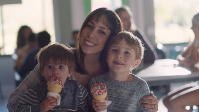 slo mo. portrait of a mother and her two sons eating ice cream together, kisses her on the cheek - family with two children stock videos & royalty-free footage