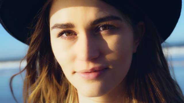 vidéos et rushes de verticale d'une fille mystérieuse dans le chapeau. apprécier le paysage marin - grognon