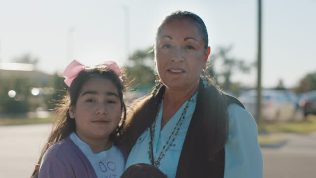 slo mo. portrait of a native american woman standing with her grandchildren - indigenous north american culture stock videos & royalty-free footage