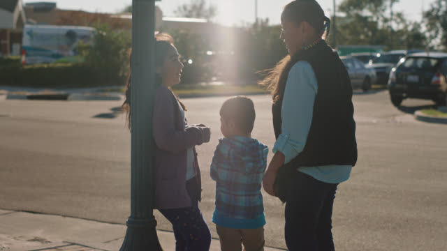slo mo. portrait of a native american woman standing with her grandchildren on a street corner - indigenous north american culture stock videos & royalty-free footage