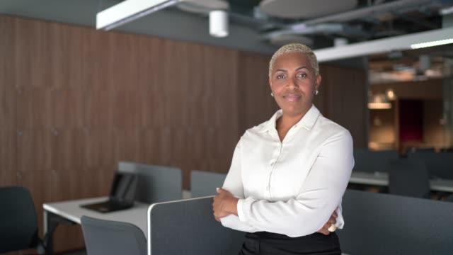 vídeos de stock, filmes e b-roll de retrato de uma empresária do orgulho de pé com os braços cruzados no escritório - braços cruzados