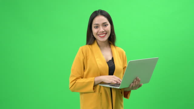 portrait of a professional young businesswoman holding laptop - green background stock videos & royalty-free footage