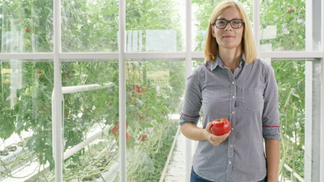 DS Portrait of a proud female gardener holding a tomato