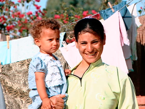 portrait of a proud smiling coptic orthodox christian mother carrying a curly headed toddler. the mother and daughter pose in front of clothes lines... - curly stock videos & royalty-free footage