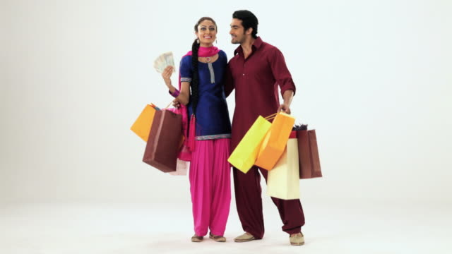 portrait of a punjabi couple showing shopping bag and money  - wealth stock videos & royalty-free footage