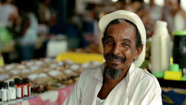 vídeos de stock e filmes b-roll de portrait of a rastafarian at a local market in martinique - pessoas ao fundo