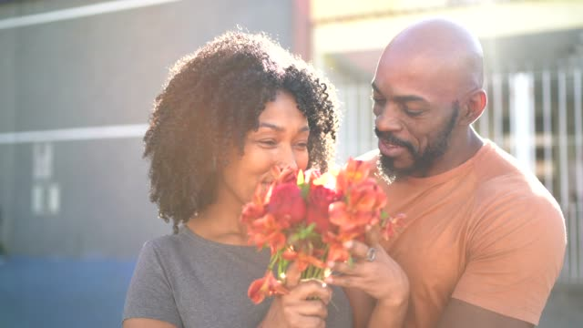 portrait of a romantic couple - husband surprising wife with flowers - giving stock videos & royalty-free footage