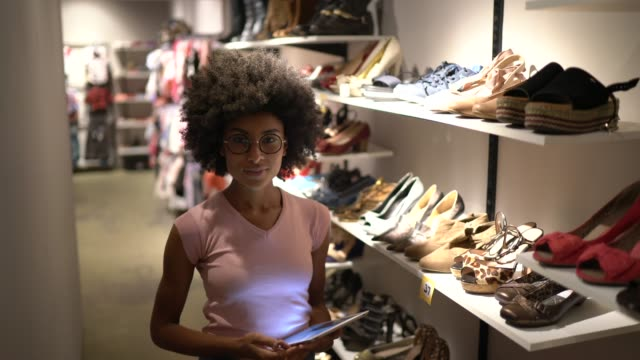 portrait of a saleswoman using a digital tablet in a store - clothes shop stock videos & royalty-free footage