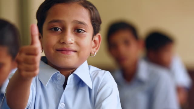 portrait of a scholgirl gesturing thumbs up in the classroom, haryana, india - thumbs up stock videos & royalty-free footage
