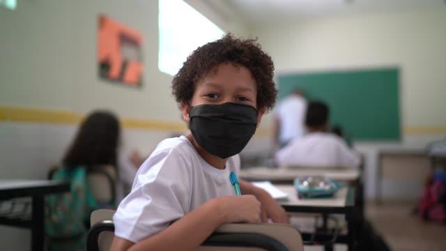 vídeos de stock e filmes b-roll de portrait of a schoolboy wearing face mask studying in classroom - américa latina