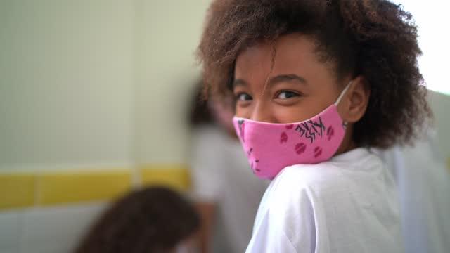 vídeos de stock, filmes e b-roll de retrato de uma aluna no corredor usando máscara facial na escola - educação
