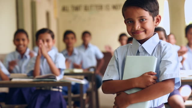 Portrait of a schoolgirl standing in the classroom, Haryana, India