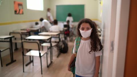 vídeos y material grabado en eventos de stock de retrato de una colegiala con máscara facial de pie en la entrada del aula - hispanoamérica