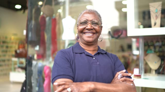 vídeos de stock e filmes b-roll de portrait of a senior business owner standing with arms crossed in front of a store - em frente de