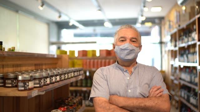 vídeos de stock, filmes e b-roll de retrato de um empresário sênior usando máscara facial de pé com os braços cruzados em uma loja de vinhos - braços cruzados