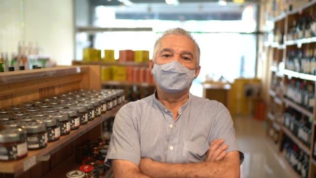ritratto di un imprenditore anziano che indossa una maschera facciale in piedi con le braccia incrociate in un negozio di vini - mercante video stock e b–roll