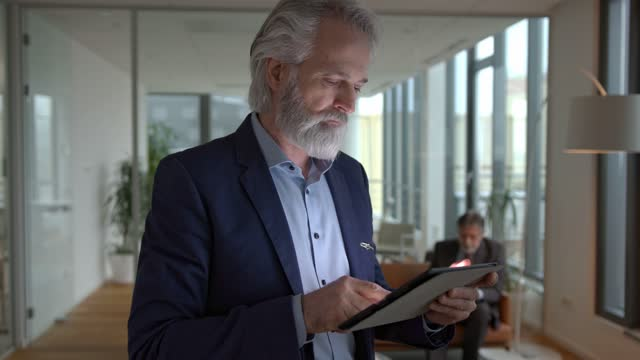portrait of a senior businessman with a digital tablet in a corporate office - full suit stock videos & royalty-free footage
