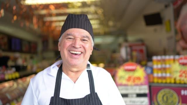 ritratto di macellaio anziano in piedi di fronte a una macelleria - mercante video stock e b–roll