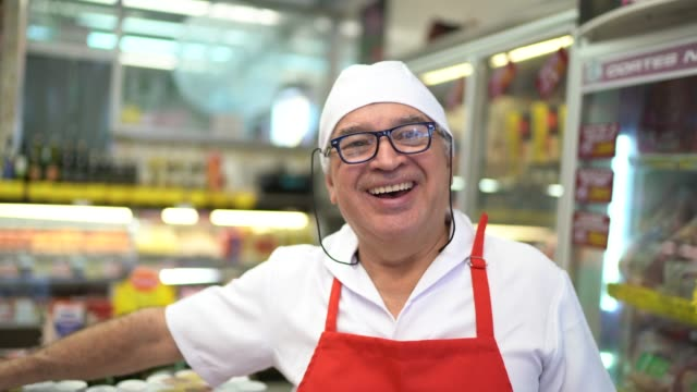 portrait of a senior butcher standing in front of a butchers shop - in front of stock videos & royalty-free footage