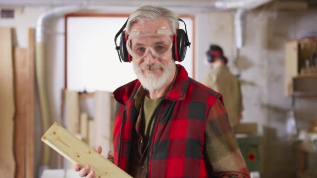 ds portrait of a senior carpenter with a grey beard smiling in his workshop - work tool stock videos & royalty-free footage