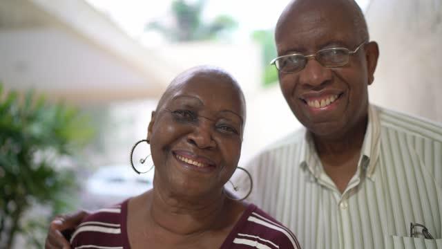 vidéos et rushes de verticale d'un couple aîné à la maison - complètement chauve