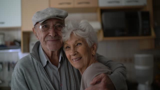 porträt eines älteren ehepaares, das sich zu hause umarmt - niedlich stock-videos und b-roll-filmmaterial
