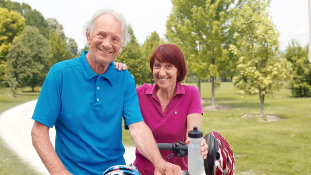 slo mo portrait of a senior couple with their bikes - cycling helmet stock videos & royalty-free footage