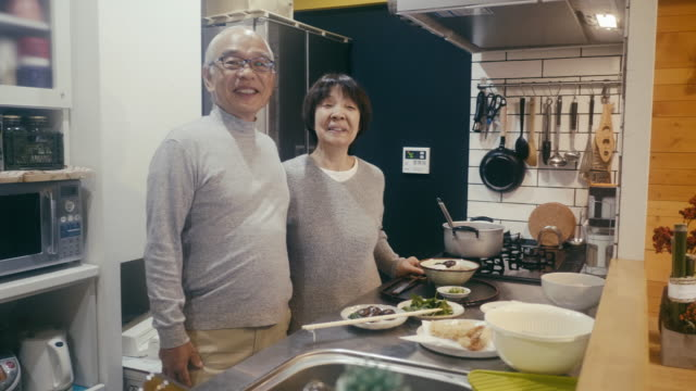 portrait of a senior couple with toshikoshi soba year-crossing noodles in the kitchen - japanese ethnicity stock videos & royalty-free footage