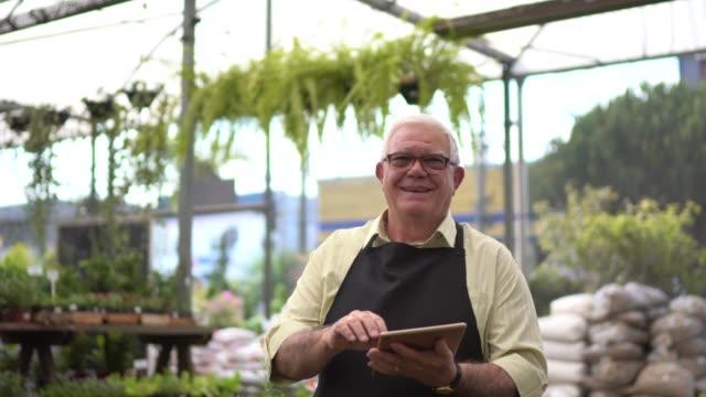 portrait of a senior florist using a digital tablet - centro per il giardinaggio video stock e b–roll