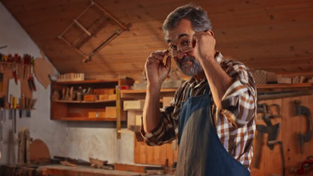 portrait of a senior male carpenter in his workshop - hobbies stock videos & royalty-free footage