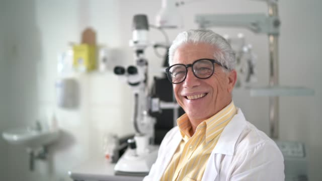 portrait of a senior male optometrist at his clinic - optometrist stock videos & royalty-free footage