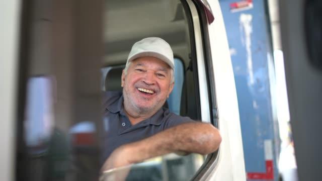 vídeos de stock, filmes e b-roll de retrato de um motorista de caminhão sênior sentado em táxi - caminhão